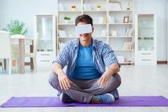 Man wearing virtual reality VR glasses meditating on floor at ho. Me Stock Image
