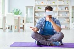 Man wearing virtual reality VR glasses meditating on floor at ho. Me Royalty Free Stock Photo