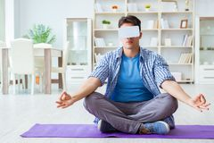 Man wearing virtual reality VR glasses meditating on floor at ho. Me Royalty Free Stock Images