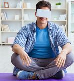 Man wearing virtual reality VR glasses meditating on floor at ho stock image