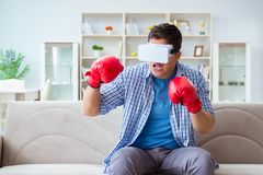 The man wearing virtual reality vr glasses playing boxing game. Man wearing virtual reality VR glasses playing boxing game Stock Images