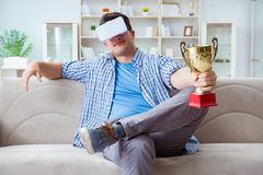 The man wearing virtual reality vr glasses receiving prize cup award Stock Photo