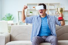 The man wearing virtual reality vr glasses receiving prize cup award. Man wearing virtual reality VR glasses receiving prize cup award Royalty Free Stock Image