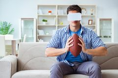 Man wearing virtual reality VR glasses watching american footbal Stock Photo