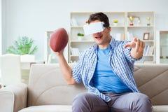Man wearing virtual reality VR glasses watching american footbal. L Stock Image