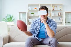 Man wearing virtual reality VR glasses watching american footbal. L Royalty Free Stock Images