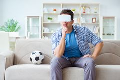 The man wearing virtual reality vr glasses watching soccer football. Man wearing virtual reality VR glasses watching soccer football Stock Photo
