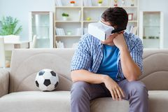 The man wearing virtual reality vr glasses watching soccer football. Man wearing virtual reality VR glasses watching soccer football Royalty Free Stock Photos