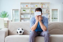 The man wearing virtual reality vr glasses watching soccer football. Man wearing virtual reality VR glasses watching soccer football Stock Photos