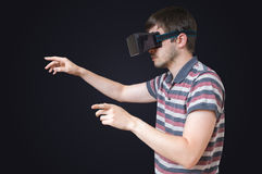 Man is wearing vr glasses and touching something on black background Royalty Free Stock Images