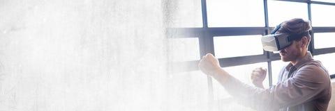 Man Wearing VR Headset by windows. Digital composite of Man Wearing VR Headset by windows Royalty Free Stock Image