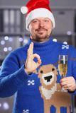 Man wearing warm blue deer sweater hold in arm champagne Royalty Free Stock Images