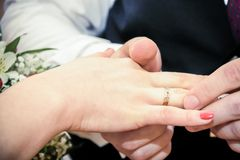 Man wearing wedding ring on bride finger. Man wearing wedding ring on a bride finger Stock Photography