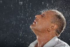 Man wearing wet shirt stands in rain. Tanned man wearing white wet shirt stands in rain and drops fall on his head. Andrei Popov is Bodybuilding Champion of Royalty Free Stock Photos
