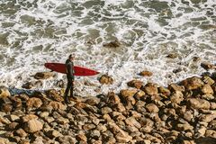 Man Wearing Wetsuit and Holding Red Surfboard on Shore Stock Photos