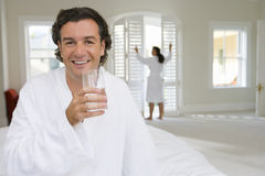 Man wearing white bath robe on bed, holding glass of water, woman standing in background. Man wearing white bath robe on bed, holding glass of water, women Stock Photos