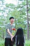 Man Wearing White and Black Striped Crew-neck Shirt Holding Red and Yellow Flowers royalty free stock image