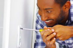 Man wearing white and blue shirt working on electrical wall socket using screwdriver, electrician concept Royalty Free Stock Image
