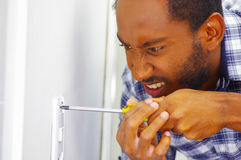 Man wearing white and blue shirt working on electrical wall socket using screwdriver, electrician concept.  Stock Image