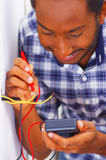 Man wearing white and blue shirt working on electrical wall socket wires using multimeter, electrician concept Royalty Free Stock Photography