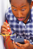 Man wearing white and blue shirt working on electrical wall socket wires using multimeter, electrician concept Stock Photos
