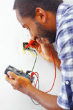 Man wearing white and blue shirt working on electrical wall socket wires using multimeter, electrician concept Stock Images
