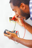 Man wearing white and blue shirt working on electrical wall socket wires using multimeter, electrician concept Royalty Free Stock Images