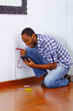 Man wearing white and blue shirt working on electrical wall socket wires using multimeter, electrician concept Stock Photography