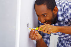 Man wearing white and blue shirt working on electrical wall socket wires using screwdriver, concentrated facial Stock Photos