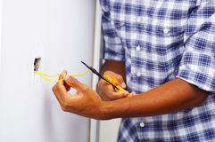 Man wearing white and blue shirt working on electrical wall socket wires using screwdriver, electrician concept Stock Image