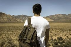 Man Wearing White Crew Neck T-shirt and Gray Backpack Standing by the Desert during Daytime Royalty Free Stock Photography