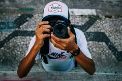 Man Wearing White Nike Sb Shirt Holding Black Dslr Camera Stock Image