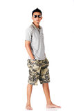 A men wearing white polo shirt and camouflage shor. A men standing and wearing a white polo shirt, camouflage shorts, sunglasses, watches and barefoot royalty free stock photos