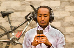 Man wearing white red business shirt sitting down with headphones on, enjoying music while looking at mobile screen. Bicycle standing behind leaning against Stock Images