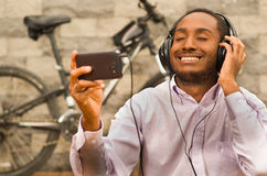 Man wearing white red business shirt sitting down with headphones on, enjoying music while looking at mobile screen. Smiling happily, bicycle standing behind Royalty Free Stock Image