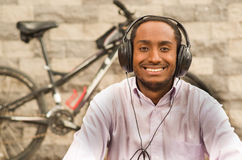 Man wearing white red business shirt sitting down, headphones on head, enjoying music looking into camera while smiling. Happily, bicycle standing behind Stock Photography
