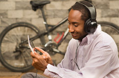 Man wearing white red business shirt sitting down, headphones on, looking at tablet screen smiling, bicycle standing Royalty Free Stock Photos