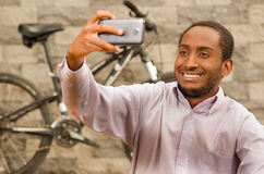 Man wearing white red business shirt sitting down, holding up mobile phone taking selfie photo, smiling and posing Royalty Free Stock Photos