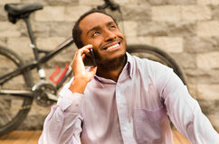 Man wearing white red business shirt sitting down, smiling and talking on mobile phone, bicycle standing behind leaning Royalty Free Stock Photo