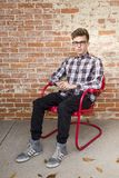 Man Wearing White And Red Long Sleeve Shirt Sitting On Red Steel Armchair Royalty Free Stock Photography