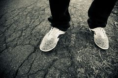 Man wearing white shoes standing in a place stock photo