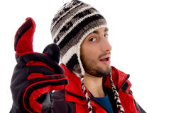 Man wearing winter cap and jacket with a pointing. Man wearing winter cap and jacket and pointing against white background Stock Image