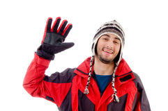 Man wearing winter cap and jacket waving hello. Against white background Stock Photos