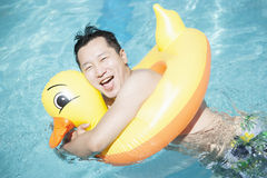 Man wearing a yellow duck inflatable tube and playing in the pool Royalty Free Stock Image