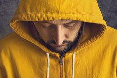 Man Wearing Yellow Hooded Jacket. Adult Bearded Man Wearing Yellow Hooded Jacket, Eyes Closed Royalty Free Stock Photos