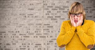 Man wearing a yellow jumper against brick wall Stock Photography