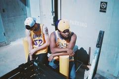Man Wearing Yellow La Lakers Jersey Sitting Next to Man Wearing Yellow Basketball Jersey Stock Photo