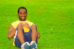 Man wearing yellow shirt and blue shorts doing situps in park sorrounded by green grass, happy facial expression Royalty Free Stock Photo