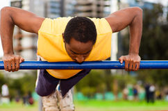 Man wearing yellow shirt and blue shorts doing static strength excercises hanging from pole, outdoors training facility Stock Images