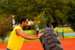 Man wearing yellow shirt and blue shorts lifting large tractor tire during strength excercise, outdoors training Stock Photo